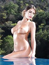 August Ames exposes her naked tits, pulls down her panties and opens her thighs and stimulates her tight pussy